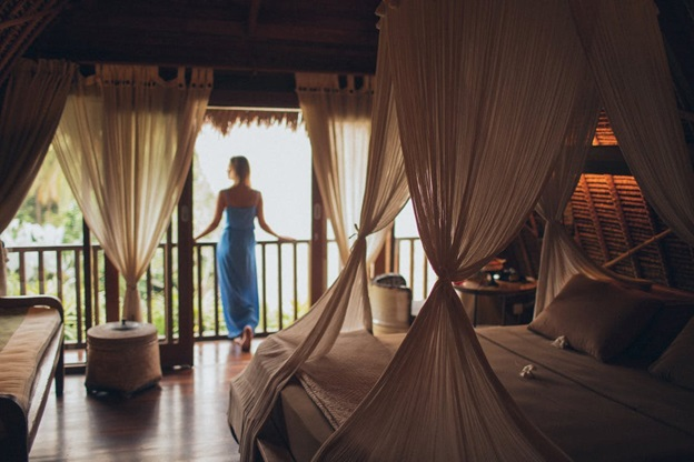 A woman standing at the balcony enjoying her luxury vacation