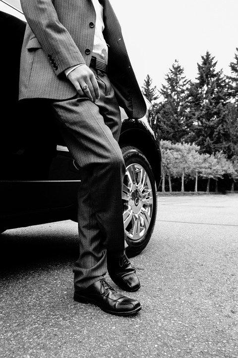 A man in a suit leaning against a car.